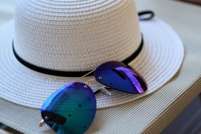 A white sunhat with a black ribbon on a table with a pair of blue lensed sunglasses